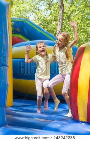 Two Girls Grimacing Happily Jumping On An Inflatable Trampoline