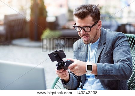 Exiting process. Joyful content smiling man holding game console and playing video games while resting