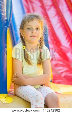 Five-year Girl Naprygalis On A Large Inflatable Trampoline Sat Down To Rest