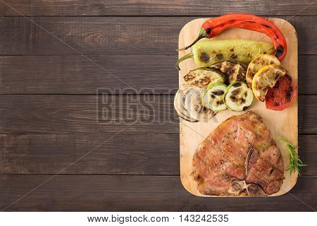 Grilled Pork Chop And Vegetables On The Wooden Background. Copyspace For Your Text