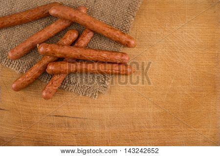 Smoked sausages on a rustic wooden chopping board close-up