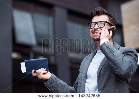 Important call. Pleasant joyful smiling man holding purse and talking on cell phone while standing near office building