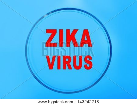 Zika virus danger concept. Petri dish with text zika virus on blue background.