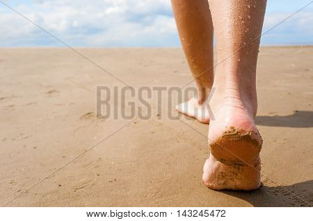 Female walking on sand beach leaving footprints in the sand. Closeup detail of female feet and golden sand.