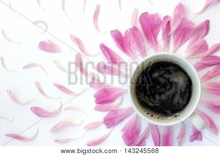 flat lay with white cup of black coffee surrounded pink petals top view / black coffee with the scent of flowers