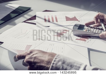Hands of unidentifiable person checking facts on various printed paper charts with calculator and pen.