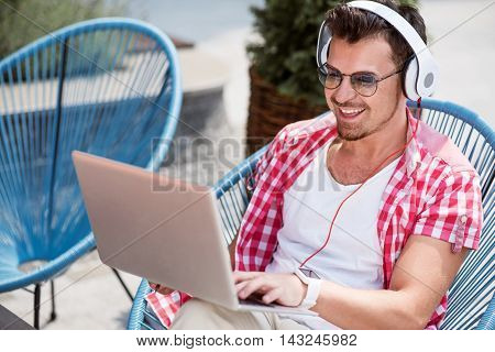 Enjoy sounding. Cheerful smiling young man sitting in the arm chair and using laptop while listening to music