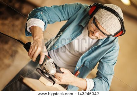 Carpenter working on a project in his workshop.A man sands piece of wood with an orbital power sander.