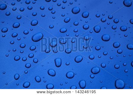 water drops on blue car body threated with protective coating, closeup photo