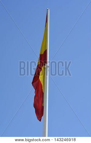 A Spanish flag against a blue sky