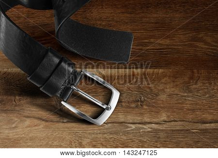 Black men's leather belt isolated on wood background. With clipping path.