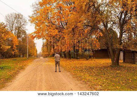 Man photographing street view of village with country road trees and wooden house at golden autumn in Belarus on cloudy weather