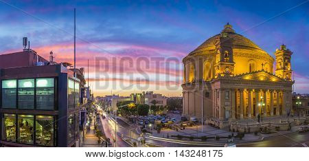 Malta - Panoramic skyline view of the famous Mosta Dome and maltese houses with amazing colorful sky at sunset