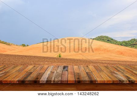 Empty wood table with view of soil preparation for crop planting on farm lands background. For display or montage your products.