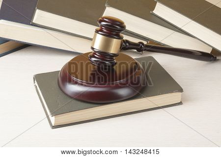 Law concept - Book with wooden judges gavel on table in a courtroom or enforcement office