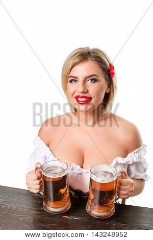 Beautiful young blond girl in dirndl drinks out of oktoberfest beer stein. Isolated on white background. sits by the table