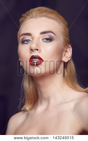 Beauty woman with creative make up and red plump lips. Portrait of beautiful young blonde girl with bright make-up. Art visage on black background.
