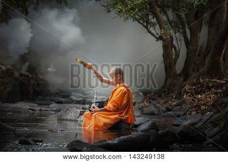 Asia novice monk in the river .