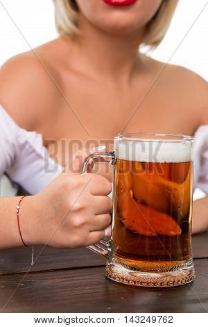 Beautiful young blond girl in dirndl drinks out of oktoberfest beer stein. Isolated on white background. sits by the table. close-up mug