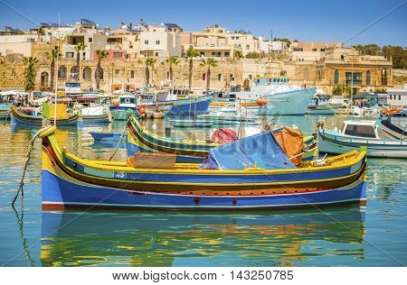 Malta - Colorful traditional Luzzu fishing boat at Marsaxlokk on a sunny summer day with green sea and blue sky