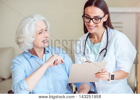 Health care. Smiling senior woman and female cheerful doctor with clipboard and stethoscope at hospital ward