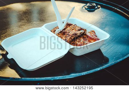Street food concept. Grilled meat on white disposable tableware, fast food items set. BBQ, grill tools. Lifestyle, eat outdoors.
