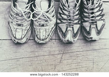 two pairs of white sports shoes on a wooden background vintage toning
