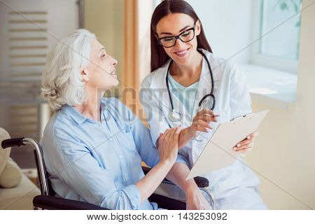 Trust. Happy senior woman and female merry and kind doctor holding clipboard and pen being at hospital ward