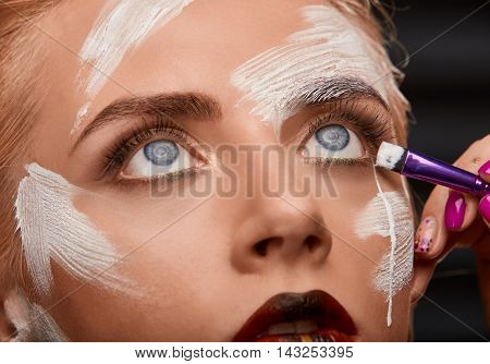 Process of bright art visage with white paint on girls the face. Beauty woman with creative make up and red plump lips. Brush makes a tear of white paint. Art visage on black background.