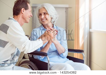 Sincere. Smiling senior mom in wheelchair and son joining hands together