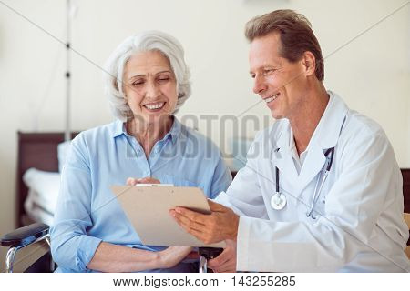 Kind doctor. Cheerful senior woman and doctor speaking with her and holding clipboard