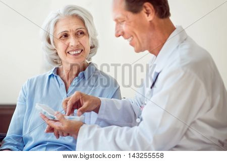 Medicines. Cheerful senior woman and positive doctor giving her medicines
