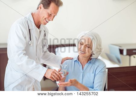 Professional help. Positive senior woman taking pills and drinking water and doctor giving her pills