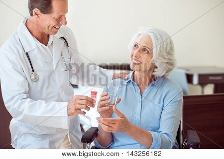 Happy aging. Cropped image of happy senior woman holding water and delighted doctor giving her these medicines