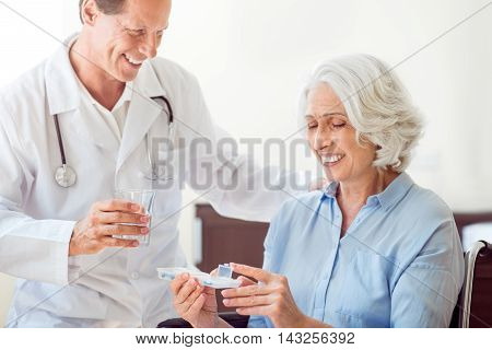 Kind of you. Cropped image of content old woman holding pills and positive helpful doctor giving water