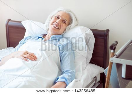 Old age. Smiling and content senior woman lying in bed being at hospital