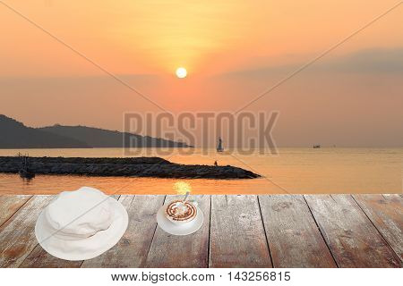 coffee cappuccino with white hat on wood table in morning sunrise at sea and space for text may be used as background space for text and may be used as background :