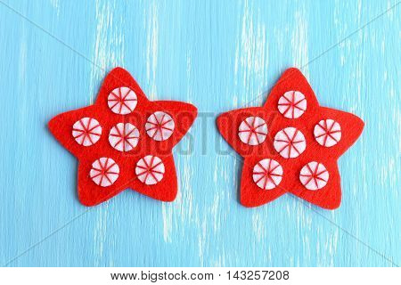 Sewing red Christmas star ornament. Sew the white felt circles to the red felt stars using red thread. Simple kids Christmas crafts. Winter hobby. Sewing instructions. Step. Top view. Closeup