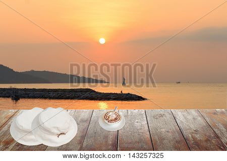 coffee cappuccino with white hat on wood table in morning sunrise at sea and space for text may be used as background
