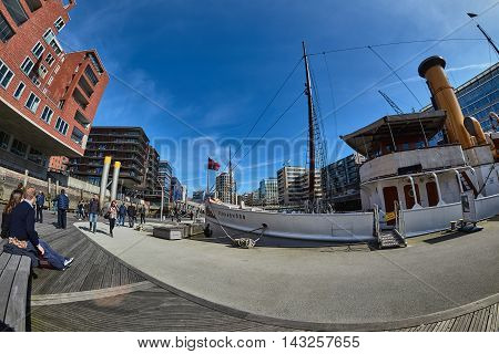 HAMBURG, GERMANY - MARCH 26, 2016: Visitors stroll through the inner of new harbor city of Hamburg and enjoy the warm weather and admire the modern architecture.