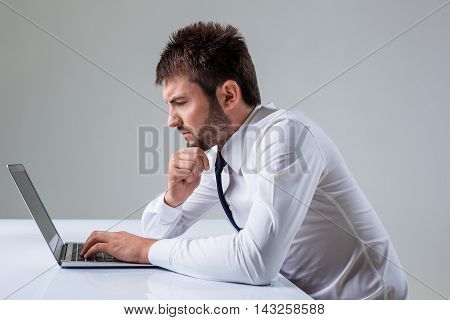 the young man stares at a laptop. It uses a computer while sitting at a table. Office clothing