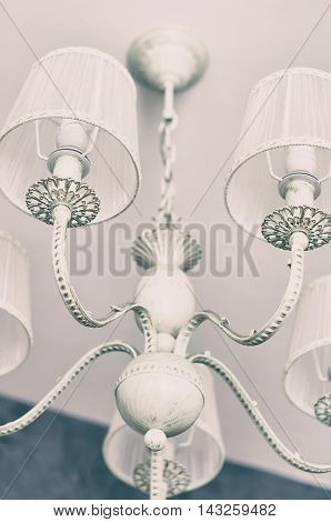 Vintage chandelier with light bulbs on the ceiling, retro filter