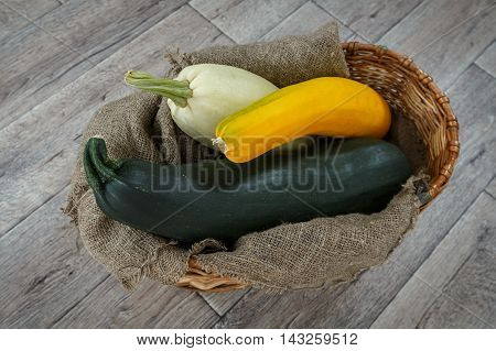 Fresh zucchini or marrow squash or courgette in basket on burlap against wooden background. Vegetables in different shapes and colors concept of diversity horizontal top view