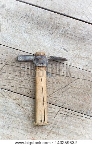 old pickaxe on a wooden background, vertical shot