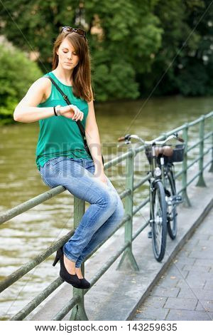 young brunette woman sitting on railing by river and looking at her watch