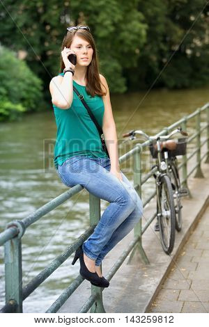young brunette woman sitting on railing by river and talking on phone