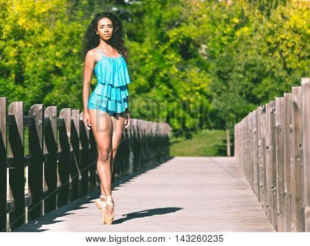 Latino dancer in second position on a bridge in a park