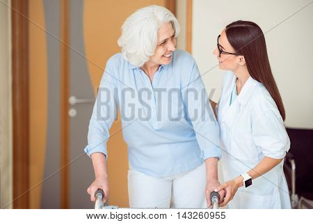 My care. Professional young cheerful doctor helping old smiling woman with walking frame
