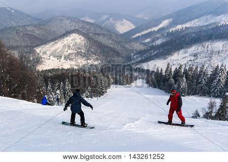 Snowboarders, descent from the mountain. Tysovets Carpathians Ukraine