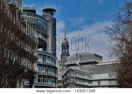 HAMBURG, GERMANY - MARCH 26, 2016: View at Gruner and Jahr headquarter building and the tower of the famous Michel in Hamburg with blue sky.